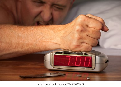 Man smashing alarm clock because he is angry at the alarm buzzer because of hangover, insomnia, work stress or snoring spouse.