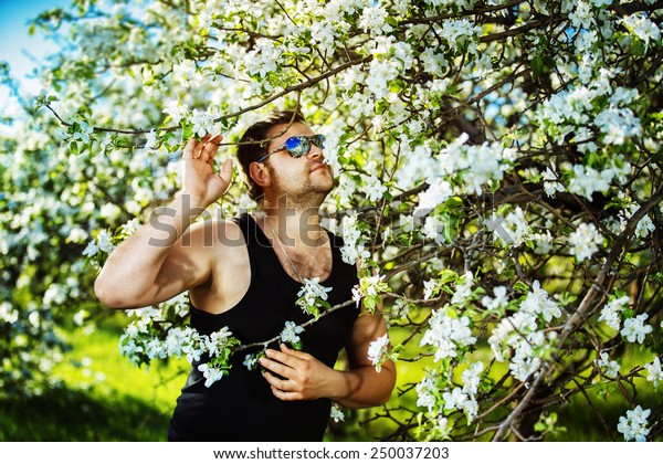 A man is smelling apple tree flowers in a morning garden.