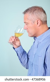 Man smelling a glass of white wine to check it's aroma