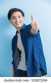man smile and show thumb up to you isolated on blue background,asian