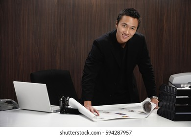 A man smiles at the camera as he rolls out plans on his desk