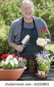 Man smiles at the camera while gardening with potted plants outdoors.