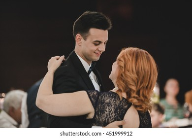 Man smiles looking at a lady while dancing