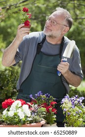 Man smiles while gardening with potted plants outdoors.