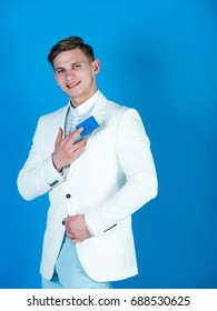 Man smiling with business or bank card. Manager wearing casual suit on blue background. Fashion and information concept. Banking and saving. Businessman posing in white jacket, shirt and pants.