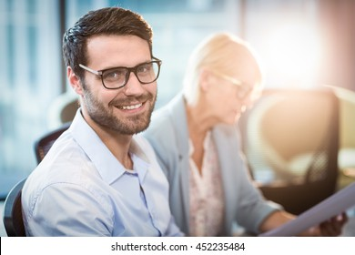 Man smiling at camera while his colleague reading document in the background