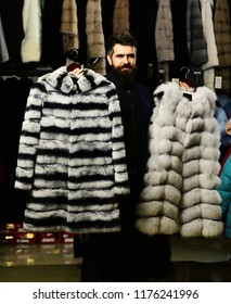 Man with smiling face holds furry coats with clothes rack on background. Luxury and stylish clothes concept. Shop assistant with expensive overcoats. Guy with beard presents furry coats.