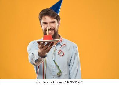 man smiling holding a birthday cake