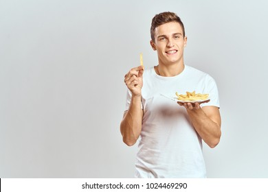 man smiling holding potatoes on a light background
