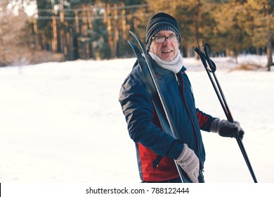 A man and smiling and holds skis and ski poles in his hands, stands in the woods in winter on snow on a sunny day