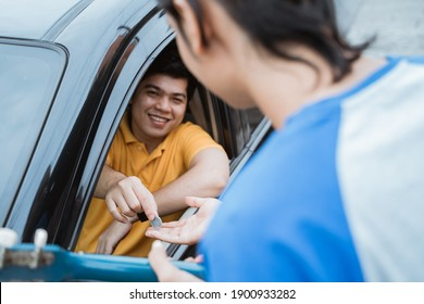 the man smiling from inside the car giving coin by hand from the car window to buskers on the road
