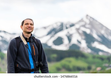 Man smiling on Snodgrass trail with camera and bokeh background view of Mount Crested Butte, Colorado peak and village in summer
