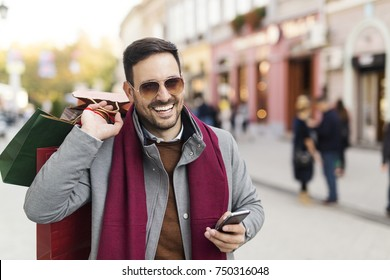 Man smiling and using phone while shopping