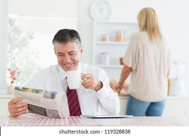 Man smiling while reading newspaper before work in kitchen drinking coffee