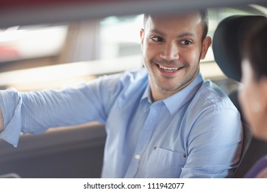 Man smiling while sitting in a car with a woman
