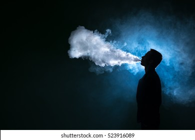 The man smoke an electric cigarette against the background of the blue light