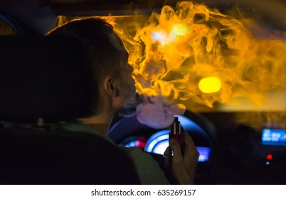 The man smoke an electrical cigarette in the car. Evening night time