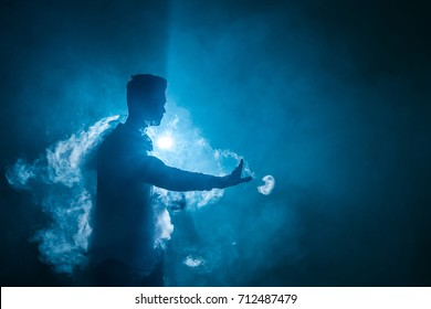 The man smoke an electrical cigarette with a ring on the dark background