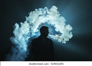 The man smoke an electronic cigarette on the dark background