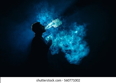 The man smoke an electronic cigarette on the background of the blue light