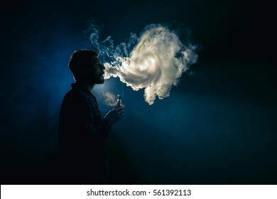 The man smoke an electronic cigarette on the background of the bright light
