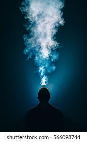 The man smoke an electronic cigarette on the background of bright light