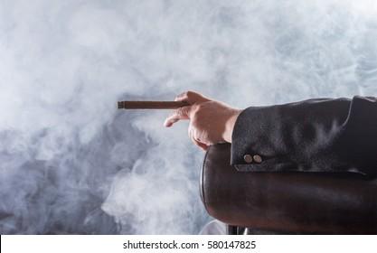 A man smokes a cigar, it smokes strongly