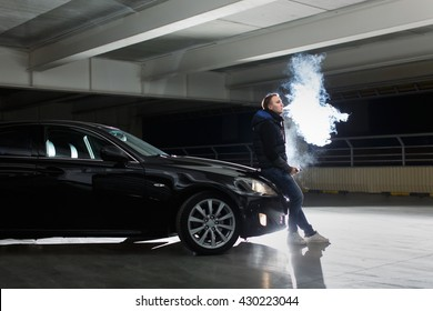 Man smokes a cigarette or hovering or vape e-cigarette. It is worth a cool to the parking lot, near his cool black car at night. backlight