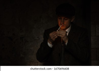 A man smokes a cigarette in the image of an English retro gangster of the 1920s dressed in a coat, suit and flat cap in Peaky blinders style.