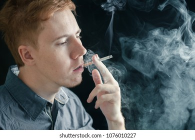 Man smokes a cigarette in smoke on a black background copy space