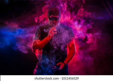 A man smokes an electronic cigarette. The man in the smoke. bearded man vaping. Men with beard in sunglasses vaping and releases a cloud of vapor. vaping man holding a mod. A cloud of vapor.
