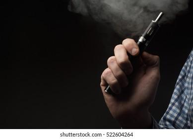 Man smokes electronic cigarette. Smoking e-cigarette. Close up shot