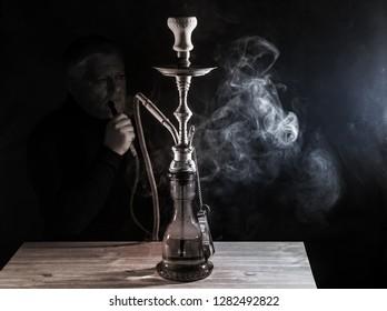 a man smokes a hookah