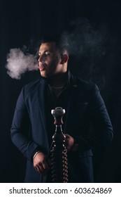 Man smokes a hookah on the dark background. The pleasure of smoking.