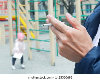 man smokes near children playground, hand with a cigarette and smoke closeup, bad habits concept
