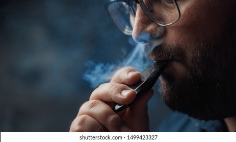 Man smokes new Vape Pod System, inhales and exhales vapor of electronic cigarette, vaping concept