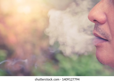 Man smoking cigarette with many smoke close up,cigarette is burning, they create more chemicals. These nicotine, tar, carbon monoxide, formaldehyde, ammonia, hydrogen cyanide, arsenic,DDT.Shallow DOF