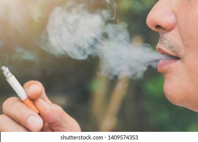 Man smoking cigarette with many smoke close up,cigarette is burning, they create more chemicals. These nicotine, tar, and carbon monoxide, formaldehyde, ammonia, hydrogen cyanide, arsenic and DDT