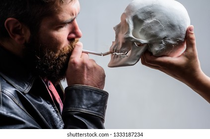 Man smoking cigarette near human skull symbol of death. Harmful habits. Destroy your health. Smoking is harmful. Habit to smoke tobacco bring harm to your body. Smoking cause health damage and death.