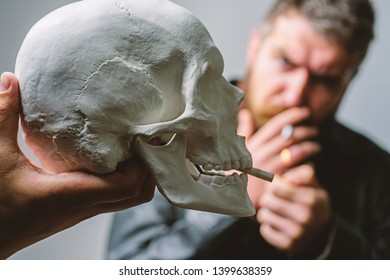 Man smoking cigarette near human skull symbol of death. Harmful habits. Smoking cause health damage and death. Destroy your health. Smoking is harmful. Habit to smoke tobacco bring harm to your body.