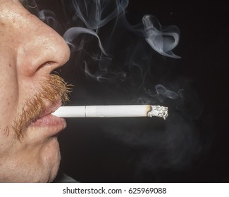 Man smoking cigarette on black background