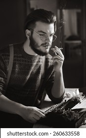 man is smoking cigarette at a table with a typewriter