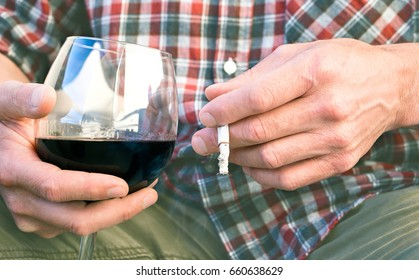 Man smoking and drinking - Close up of adult male hands holding red wine glass and  cigarette next at genital organs area as concept of male erectile dysfunction related to smoke and alcohol abuse
