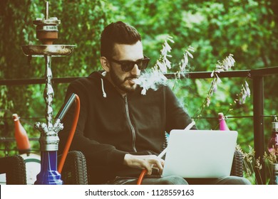 Man smoking hookah outside