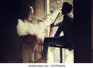 A man smoking hookah and sexy girl sitting nearby