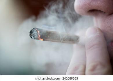 Man smoking marijuana cigarette soft drug in Amsterdam, Netherlands