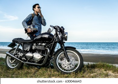 man smoking a motorcycle riding on the beach