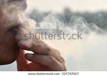 man smoking in nature