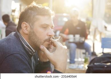 Man Smoking On Bright Sunny Day Outdoor