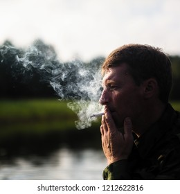 Man smoking outdoor, close-up. Smoke in the background light.